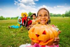 Happy African girl holds Halloween pumpkin stock photography