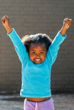 Happy african girl raising arms high. Stock Photos