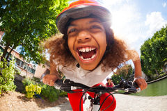 Happy African girl riding her bicycle at sunny day. Close-up portrait of smiling African girl in safety helmet riding her bicycle at sunny day in full speed royalty free stock images