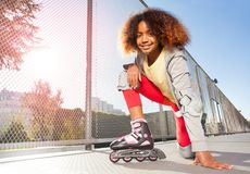 Happy African girl posing on floor at skate park stock photography
