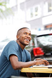 Happy african guy sitting at a cafe Royalty Free Stock Images