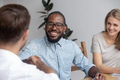 Happy african hr recruit handshake hire candidate at job interview royalty free stock image