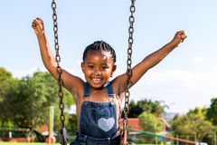 Happy African kid raising arms on swing. Royalty Free Stock Photos