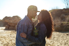 Happy african loving couple hugging outdoors at beach. Picture of happy african loving couple walking outdoors at beach while hugging. Looking aside Royalty Free Stock Photos