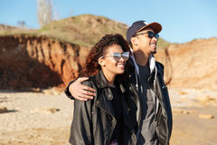 Happy african loving couple walking outdoors at beach Royalty Free Stock Images