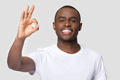 Happy african male showing ok sign pose on grey background royalty free stock photography