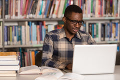 Happy African Male Student With Laptop In Library. In The Library - Handsome African Male Student With Laptop And Books Working In A High School - University Stock Photography