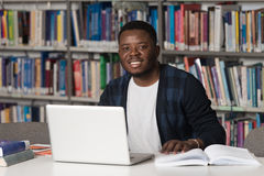 Happy African Male Student With Laptop In Library Royalty Free Stock Images