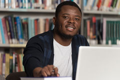 Happy African Male Student With Laptop In Library Royalty Free Stock Photography
