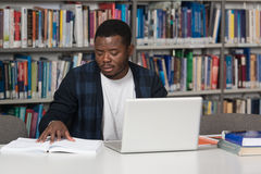 Happy African Male Student With Laptop In Library Stock Images