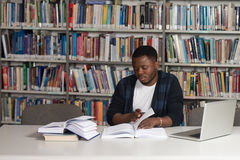 Happy African Male Student With Laptop In Library Stock Photos