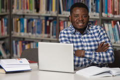 Happy African Male Student With Laptop In Library Stock Photography