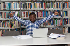 Happy African Male Student With Laptop In Library. In The Library - Handsome African Male Student With Laptop And Books Working In A High School - University Royalty Free Stock Photography