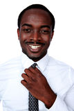Happy african man adjusting his necktie Stock Photo