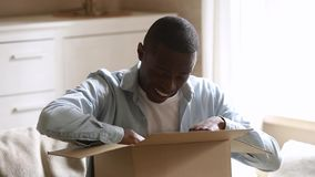 Happy african man customer open parcel cardboard box at home stock video footage