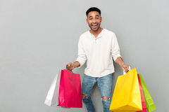 Happy african man holding shopping bags. stock images