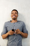 Happy african man lying down listening to music with cellphone Royalty Free Stock Image