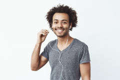 Happy african man putting out headphone lookig at camera smiling. White background. Stock Image