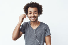 Happy african man putting out headphone lookig at camera smiling. White background. Stock Photography