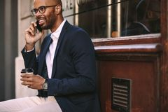 Happy african man talking on phone outdoors. Happy african man relaxing outdoors with coffee and talking on mobile phone. Young man in business suit sitting stock photos
