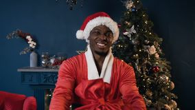 Happy african man in santa claus costume holding the gift on the Christmas tree background. Happy african man in red santa claus costume with cap giving the stock video footage
