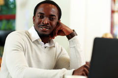 Happy african man sitting at the table Stock Images