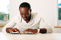 happy african man sitting on the table Stock Photos