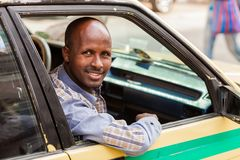 Happy African man sitting in a taxi, smiling straight at the cam stock photography