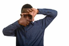 Happy African man smiling and focusing with fingers at camera. Isolated against white background stock photo