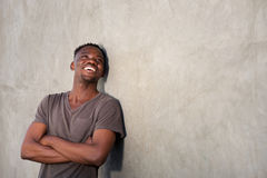 Happy african man smiling by wall and looking at copy space Stock Photos