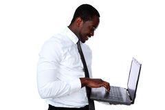 Happy african man standing and using laptop Royalty Free Stock Photos