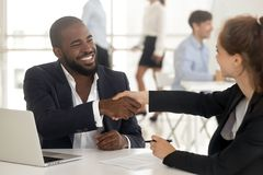 Happy african manager broker handshaking caucasian client at meeting. Happy african american manager broker agent handshake caucasian client at meeting, diverse royalty free stock photo