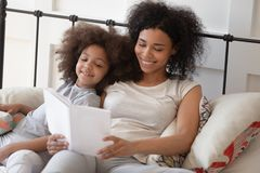Happy african mother reading book relaxing in bed with daughter royalty free stock photos