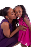 Happy african mother kissing her daughter. Isolated on white background Stock Images