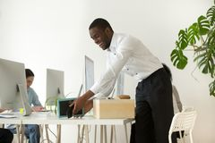 Happy african new employee unpacking belongings on first working. Happy african new employee unpacking box with belongings at workplace on first working day stock photo