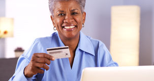 Happy african senior approved with new credit card. Happy Mature African woman approved with new credit card royalty free stock images