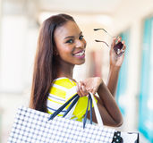 Happy african shopper. Happy attractive african shopper in shopping mall royalty free stock images