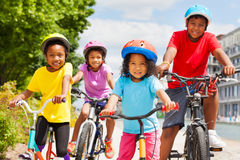 Happy African siblings riding bikes in summer city. Portrait of four happy age-diverse African children in safety helmets riding bikes in summer city Stock Photos