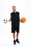 Happy african sports man holding basketball and soccer ball Stock Photos