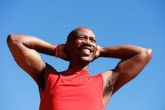 Happy african sports man standing against sky Stock Photo