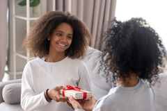 Free Happy African Teen Daughter Give Birthday Gift Box To Mum Royalty Free Stock Image - 173474376