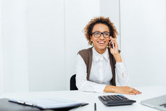 Happy african woman accountant sitting and talking on cell phone Stock Photo