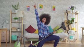 Happy african woman with an afro hairstyle plays the mop of the vacuum cleaner like a guitar slow mo. Happy african woman housewife with an afro hairstyle plays stock footage