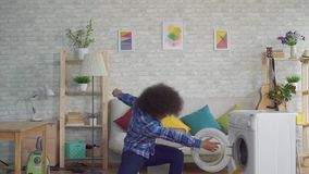 Happy african woman with an afro hairstyle throws dirty clothes in the washing machine like a ball in the basket slow mo. Happy african woman with an afro stock footage