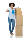 Happy african woman with boxes showing thumbs up Stock Photography