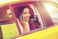 Happy african woman calling on smartphone in taxi Stock Photo