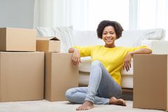 Happy african woman with cardboard boxes at home Stock Photography