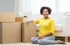 Happy african woman with cardboard boxes at home Stock Photos