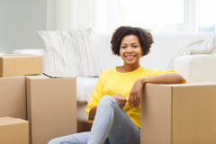 Happy african woman with cardboard boxes at home Royalty Free Stock Image