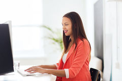 Happy african woman with computer at office Royalty Free Stock Image